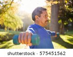 mature man exercising with... | Shutterstock . vector #575451562