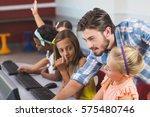 teacher assisting schoolgirls... | Shutterstock . vector #575480746