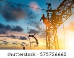 Silhouette electrician work installation of high voltage in high voltage stations safely and systematically over blurred natural background. - stock photo
