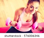 woman lifting two dumbbells.... | Shutterstock . vector #576006346