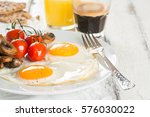 Small photo of Breakfast of sunny side up eggs with mushrooms and tomatoes, coffee and orange juice on white wooden background