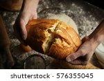 male hands breaking freshly... | Shutterstock . vector #576355045