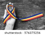 Small photo of Red Yellow Blue Trisomy Awareness Month ribbon in March on helping hand on grunge aged background (clipping path)
