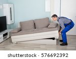 male mover placing sofa on... | Shutterstock . vector #576692392