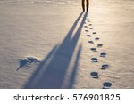 Fresh boots footprints with human shadow in the snow in the sunset light in winter evening. Background. - stock photo