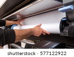 Small photo of Close-up man hands loading wide format white paper roll on professional printer