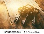 Small photo of close up image of vintage skeleton keys over wooden table and bright light as revelation concept