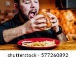 young man eating a cheeseburger.... | Shutterstock . vector #577260892