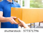 Small photo of Delivery man in blue uniform handing parcel boxes to recipient - courier service concept