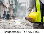 Small photo of Engineer or Safety officer holding hard hat with the heavy equipment excavator demolition demolish machine in construction site.