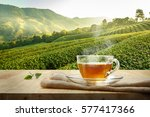 Stock photo warm cup of tea and tea leaf and sack on the wooden table and the tea plantations background 577417366