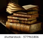 Small photo of Vintage books stack on old wooden surface in warm directional light. Selective focus.