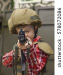 Small photo of young boy in military uniform with riffle takes aim to camera