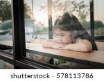 Small photo of Asian girl Undeterred vacant, sitting in a cafe.The view from the glass