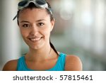 Portrait of a female swimmer wearing swimming goggles and smiling - stock photo