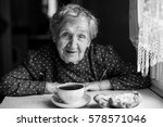 elderly woman drinking tea.... | Shutterstock . vector #578571046