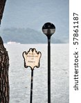 Idyllic Italian waterfront in Domaso at Lake Como with old streetlight, pedestrian area sign and pine tree, passenger boat in the background - stock photo