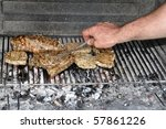 View into a stone BBQ with steaks and ribs above well burned coal - male hand is turning the steaks with a fork - stock photo