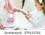 Partial view of cute little girl putting jewelry on hand of her mother on Mothers Day