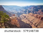 A male hiker is standing on a steep cliff taking in the amazing view over famous Grand Canyon on a beautiful sunny day with blue sky in summer, Grand Canyon National Park, Arizona, USA - stock photo