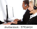 A man and a woman wearing headphones working on computers - stock photo