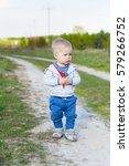Small photo of A small, alone, sad, alone year old child, a boy, walks on the path in the countryside on asunny day, keeps flower, dandelion, plant.