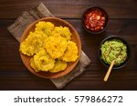 Small photo of Patacon or toston fried and flattened pieces of green plantain, traditional snack or accompaniment in the Caribbean, guacamole and tomato onion salad beside, photographed overhead with natural light