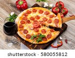 photo of a hot pizza on wooden... | Shutterstock . vector #580055812