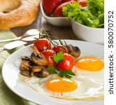 Small photo of Breakfast of sunny side up eggs with mushrooms and tomatoes, coffee and orange juice on wooden background