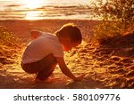 Boy Playing With Sand On The...