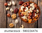 nuts mixed in a wooden plate... | Shutterstock . vector #580226476