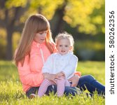 mother and daughter walking in... | Shutterstock . vector #580262356
