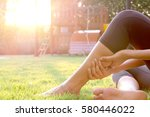 Small photo of Woman leg pain, leg pain Sitting up on the grass in the playground. The morning sun light, healthy concept.