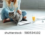 Stock photo close up of young woman petting a cat 580534102
