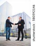 two businessmen shaking hands... | Shutterstock . vector #580592146