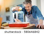 mature man in kitchen cooking... | Shutterstock . vector #580646842