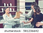 cheerful female jeweler handing ... | Shutterstock . vector #581236642