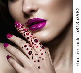 Small photo of Beautiful girl with evening make-up, purple lips in rhinestones and design manicure nails. beauty face. Photos shot in studio. Close up