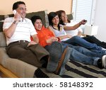 Family reclining in bed smiling at television - stock photo