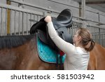 Small photo of Woman saddling horse with saddle from leather