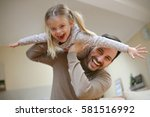 cute young daughter on a piggy... | Shutterstock . vector #581516992