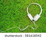White Headphones On Green Gras...