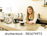 Portrait of a gorgeous young Hispanic barista leaning on the counter in front of a cup of cappuccino in a coffee shop - stock photo
