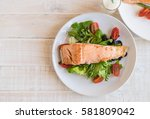 grilled salmon steak with salad | Shutterstock . vector #581809042