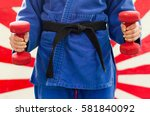 Small photo of Close Up of Woman in Blue Judo Gi, and Black Belt, which is Train with weights and kettlebells Girya
