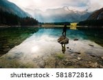 Small photo of Tourist standing and admiring the beauty of the crystal clear water lake of Laghi di fusini. In the background the magestic Mangart mountain. North Italy, Europe.