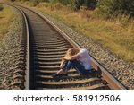 Small photo of Depressive woman sitting on a railway track