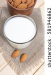 Small photo of Almond milk with almond on a wooden table - vegan drink.