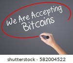 Small photo of Woman Hand Writing We Are Accepting Bitcoins with black marker on visual screen. Isolated on grey. Business concept. Stock Photo