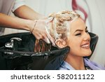 Small photo of Young blonde woman enjoying hair treatment.